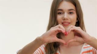 Attractive girl showing heart shape gesture