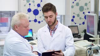 Attractive male scientist showing something on his tablet to his coworker at the laboratory. Two caucasian men in white coats looking at the tablet screen. Gray senior man holding his hands crossed on