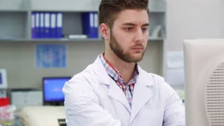 Attractive male scientist working at the laboratory. Caucasian lab worker looking at the computer screen. Close up of young bearded man in white coat with serious face