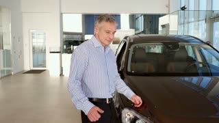 Attractive mature man showing his thumb up near the car at the dealership. Middle aged gray client approving new black SUV. Caucasian male client holding his hand on the car hood