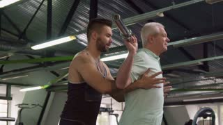 Attractive senior man squating with bar at the gym. Aged caucasian sportsman training his legs. Young bearded trainer standing behind his old client