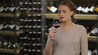 Attractive woman testing wine in the glass