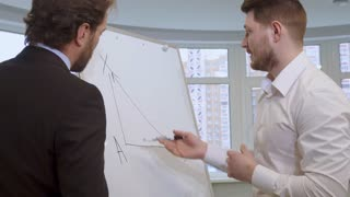Attractive young businessman drawing on the flip chart. Handsome bearded man in white shirt explaining something to his partner. Middle aged caucasian male manager in suite listening to his colleague