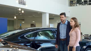 Attractive young couple choosing car at the dealership. Caucasian man and woman standing against background of black sedan. Brunette bearded guy and his pretty girlfrined looking at one of the car