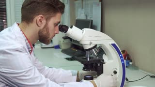 Attractive young man in white coat looking through the scope at the laboratory. Side view of caucasian male scientist probing some testing material through the microscope. Brunette bearded lab worker