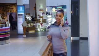 Attractive young woman using cellphone at the shopping. Pretty african american girl walking along the mall. Close up of brunette female shopper holding shopping bags with purchases in her hand