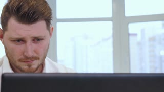 Bearded male manager using laptop on his desk. Close up of young male manager working at the office. Attractive bearded man in white shirt typing on keyboard