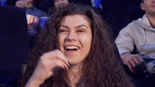Beautiful caucasian girl laughing at the movie theater. Close up of pretty curly woman putting popcorn flake into her mouth. Attractive female film viewer having fun at the cinema