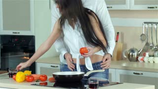 Beautiful girl doing cutting tomatoes, guy holding her by the waist