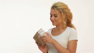 Beautiful mulatto girl shaking a gift present