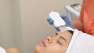 Beauty specialist making ultrasonic peeling for female client's face at the cosmetology center. Cosmetologist moving peeler along the woman's forehead. Close up of pretty asian girl cleaning her
