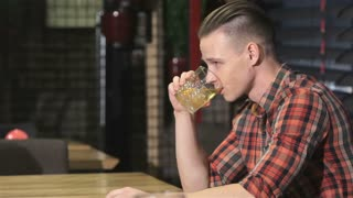 Blonde man drinks alcohol at the bar