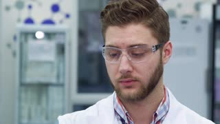 Brunette bearded man in white coat holding test in his hands. Close up of young male scientist spinning the test-tube at the laboratory. Attractive bearded lab worker peering at the testing material