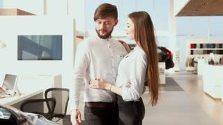 Brunette bearded man pointing his hand on the car at the dealership. Young caucasian man consulting with his pretty girlfriend at the car showroom. Attractive brown haired girl agreeing with her