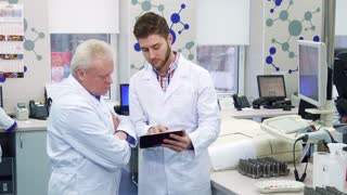 Brunette young man showing something on monitor to his colleague at the laboratory. Gray senior scientist looking at what his intern demonstrating. Brunette lab worker holding tablet in his hands