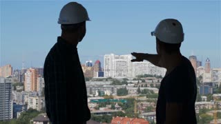 Builder points his hand at the complex of high buildings