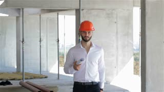 Builder walking with set of plans under his arm