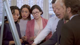 Business people of different ages looking at the flip chart. Mature women in glasses pointing their hands at the flip chart. Female manager facing the camera while their male colleagues standing