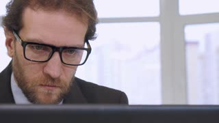 Caucasian bearded businessman looking at laptop screen. Close up of middle aged attractive male manager sitting at the table against background of window. Handsome man in suite and tie doing his