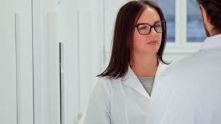 Caucasian female doctor in glasses agreeing with her male colleague. Attractive brunette woman in white coat nodding at the hospital. Male medical specialist standing backwards near his female