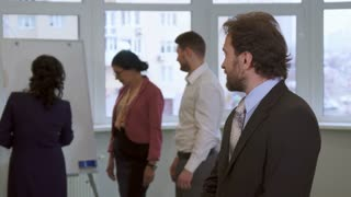 Caucasian middle aged businessman posing at the office. Attractive bearded man turning from his partners to the camera. Young guy in white shirt and two brunette women working with flip chart