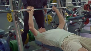 Caucasian senior man training his chest muscles. Old gray sportsman pull up the bar on the bench. Close up of young male trainer ensuring his aged client at the gym