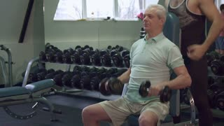 Caucasian trainer keeping his hands on the elbows of senior client. Old sportsman sitting on fitness chair at the gym. Aged gray man doing exercises with dumbbells