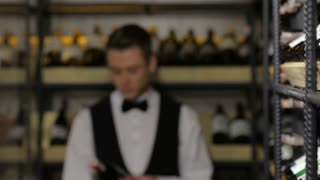 Cheerful young sommelier holding a wine bottle