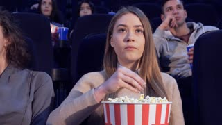 Close up attractive girl putting popcorn into her mouth at 6the movie theater. Young caucasian woman holding a bucket of popcorn in her hands. Pretty female viewer freezing for a moment while eating