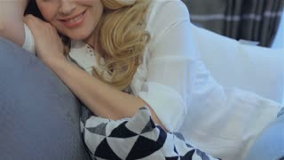Close up of attractive blond woman lying on the pillow at home. Beautiful caucasian woman holding her head on her hand. Pretty young woman lying on her body side