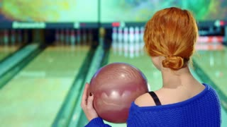 Close up of attractive caucasian girl smiling with bowling ball in her hands. Beautiful redhead woman turning to the lane. Attractive female bowler swinging before release