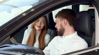 Close up of attractive caucasian man showing car key through the window. Nice young couple sitting inside the new car at the dealership. Handsome bearded man sticking his hand out of the vehicle