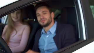 Close up of attractive caucasian man showing car key through the window. Young couple sitting in the car at the dealership. Brunette bearded guy sticking his arm out of the car window