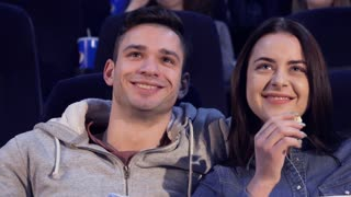 Close up of attractive young couple laughing at the movie theater. Caucasian girl and her boyfriend watching funny comedy at the cinema. Pretty female viewer tilting her head forward