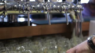 Close-up of barman hand pouring a lager beer