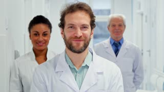 Close up of bearded male doctor showing his thumb up. Young caucasian man in white coat standing against background of african american female doctor and senior gray male doctor. Three medical