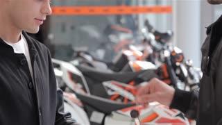 Close up of buyer getting motorbike key