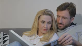 Close up of lovely caucasian couple watching photo album at home. Pretty blond woman turning page of photo album. Attractive bearded man commenting photos from photo album