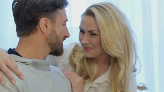 Close up of romantic couple posing at home. Nice portrait of lovely caucasian couple smiling for the camera. Brunette bearded man and pretty blond woman gently expresing their feelings to each other