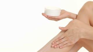 Close up of woman creams her leg