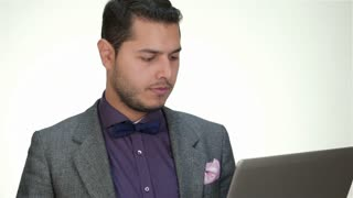 Clothed formally male working on a laptop
