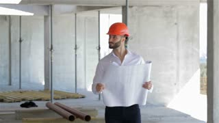 Construction engineer walks through the building under construction