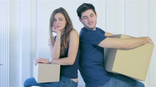 Couple girl and the guy looking each other among boxes