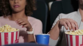 Couple in cinema theater eating popcorn