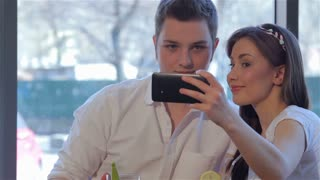 Couple poses to a selfie at the cafe