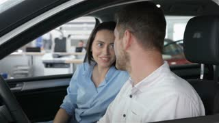 Couple talks inside the car at the dealership
