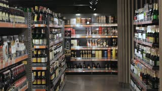 Couple walk through the alcohol section of hypermarket