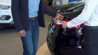 Customer getting car key at the dealership. Close up of male hands shaking against background of new cars. Two men standing near black sedan at the car showroom