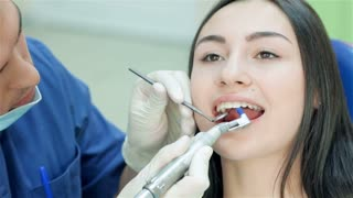 Dentist finishes viewing teeth patient girl