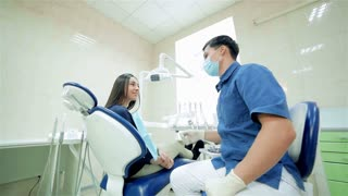 Dentist in the mask says to the patient, then they show a thumbs up to the camera